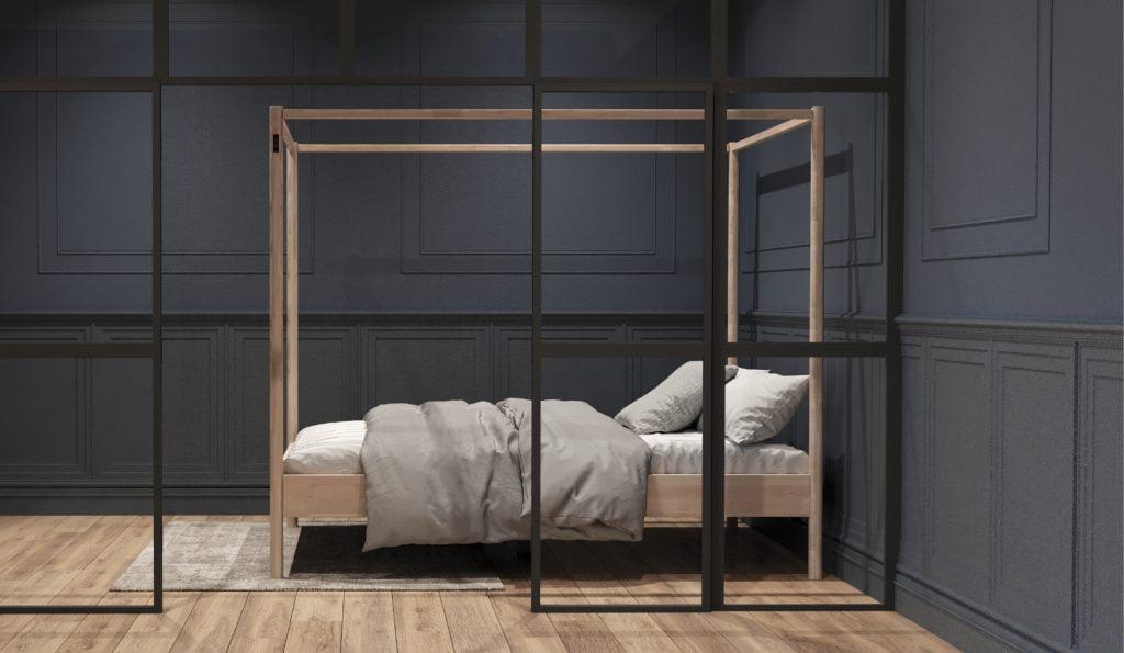 Puinen sänky tummaseinäisessä huoneessa